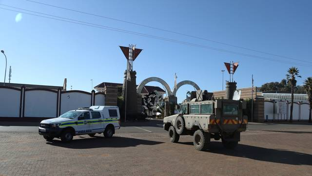 A police and a military vehicle are seen parked, as they keep watch outside a church