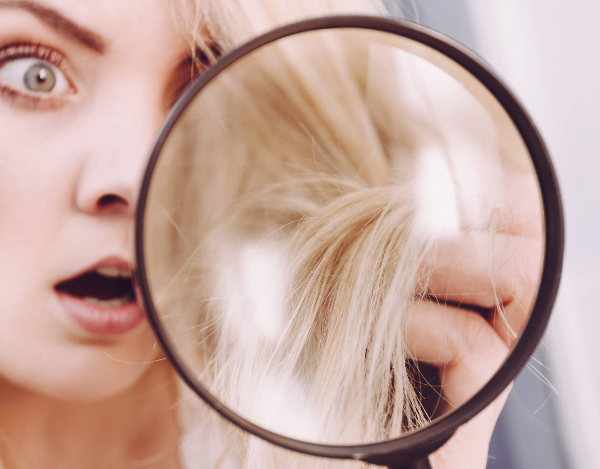 Woman looking at hair ends through magnifying glass