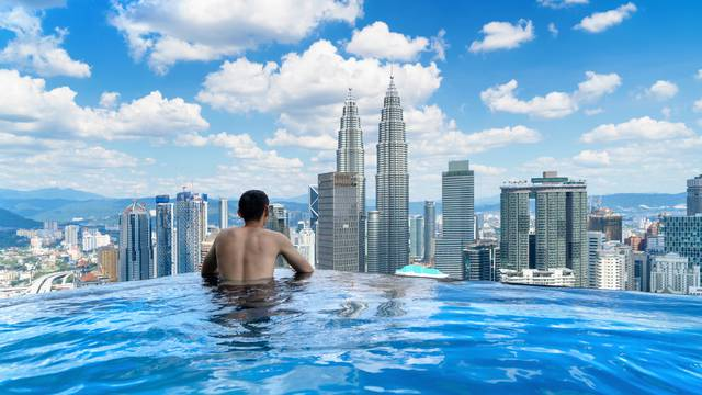 Back of tourist in a swimming pool on rooftop with Kuala Lumpur downtown view and blue sky. Malaysia travel trip in vacation and holidays concept in Asia. Skyscraper and high-rise buildings at noon.