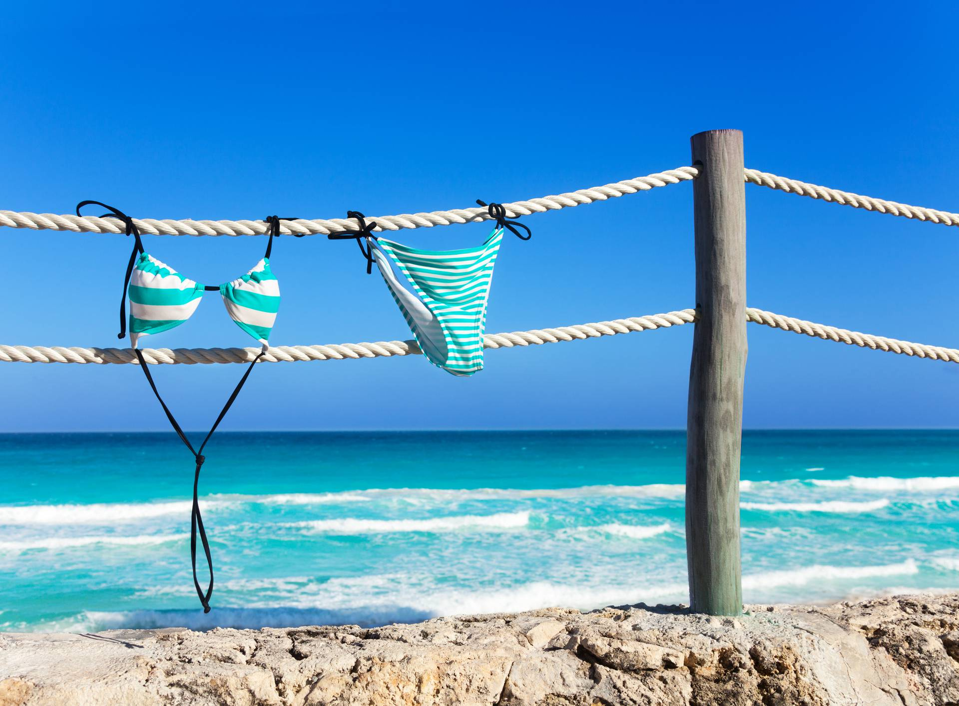 Blue woman's swimming suit hanging on white ropes