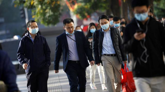 People wearing masks following the coronavirus disease (COVID-19) outbreak are seen on a street during morning rush hour in Beijing