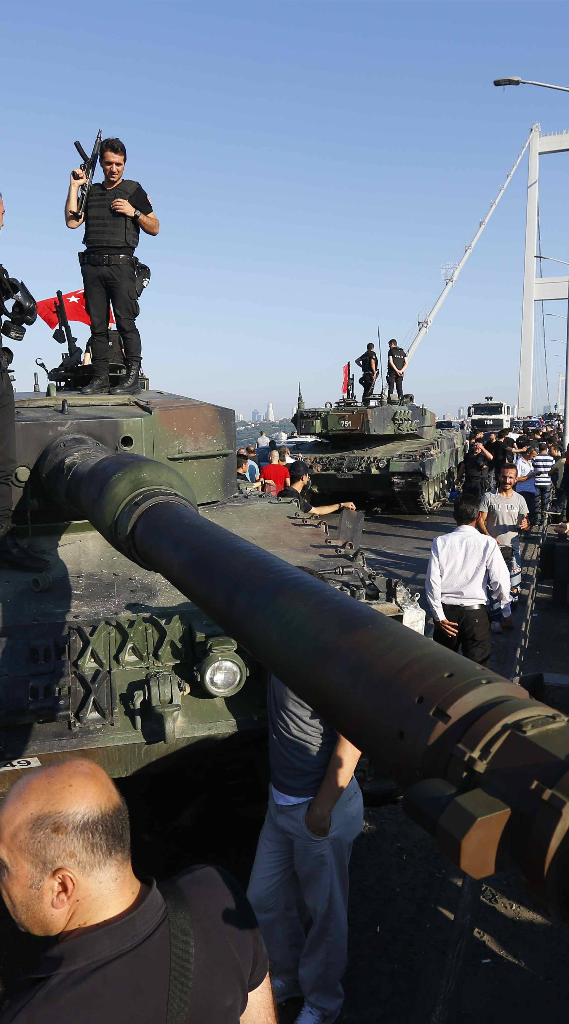 Policemen stand on a military vehicle after troops involved in the coup surrendered on the Bosphorus Bridge in Istanbul