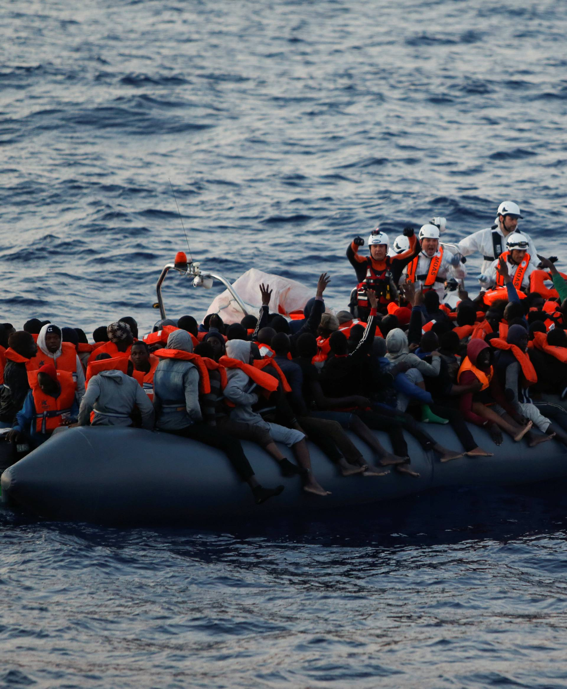 Rescuers of MOAS hand out life jackets to migrants on board a rubber dinghy in the central Mediterranean north of Sabratha on the Libyan coast