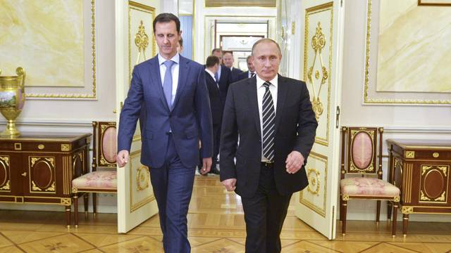 Russian President Vladimir Putin and Syrian President Bashar al-Assad enter a hall during a meeting at the Kremlin