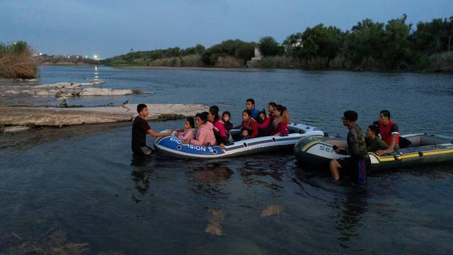 FILE PHOTO: Asylum-seeking migrants cross the Rio Grande river in Roma