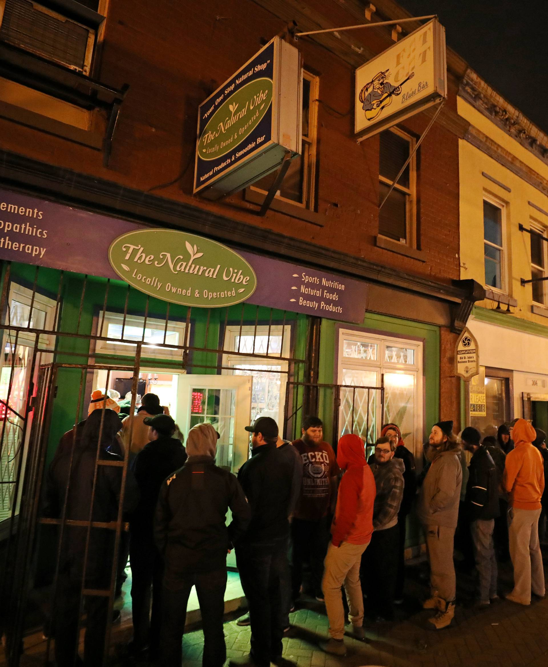 Customers line up outside the Natural Vibe store after legal recreational marijuana went on sale in St John's