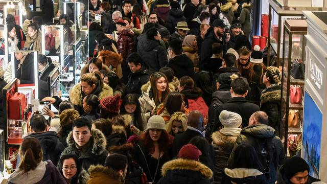 A large crowd of people shop during a Black Friday sales event at Macy's flagship store in New York City