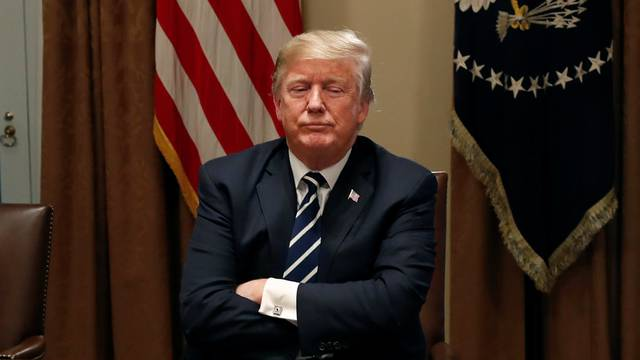U.S. President Trump waits for reporters to leave the room after speaking about his summit with Russia's President Putin in meeting at the White House in Washington