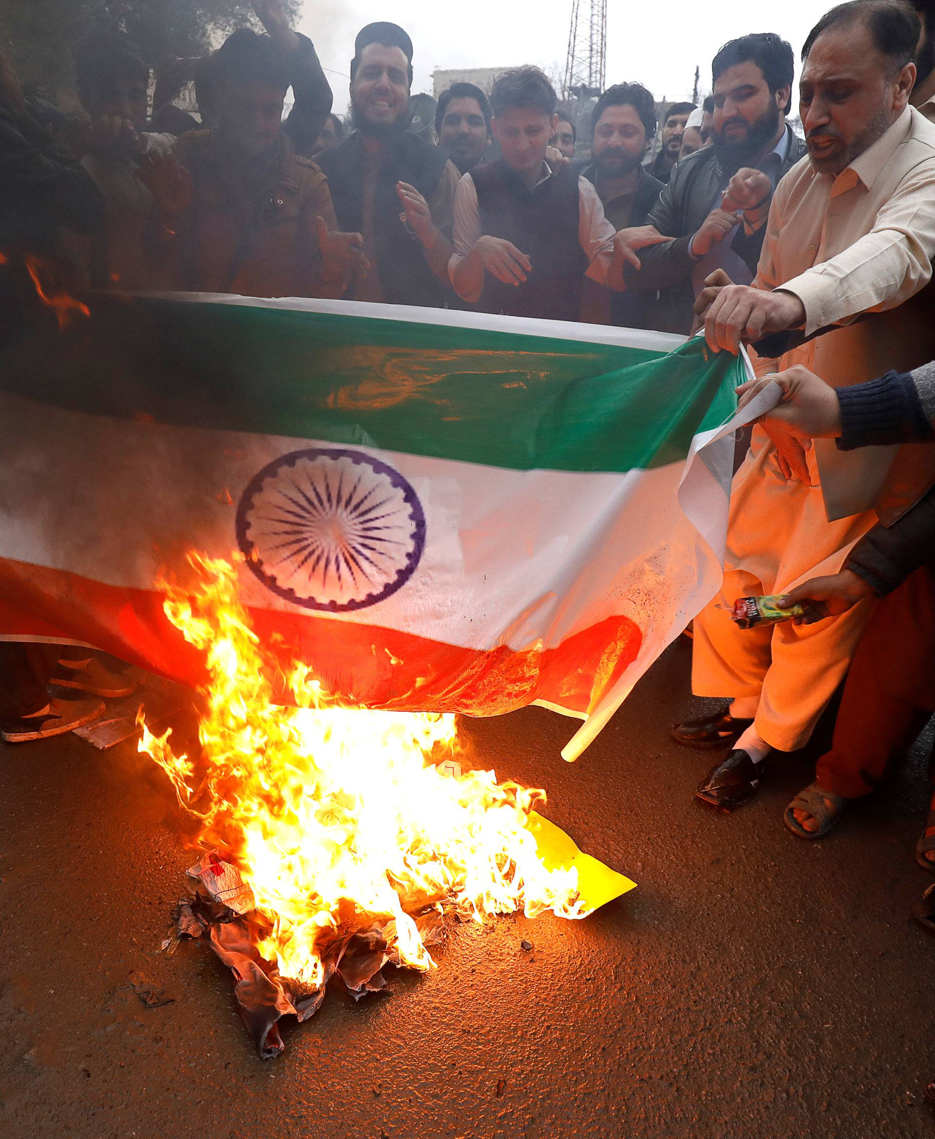People burn a poster depicting India's flag against what they call airspace violation by the Indian military aircrafts, in a protest in Peshawar