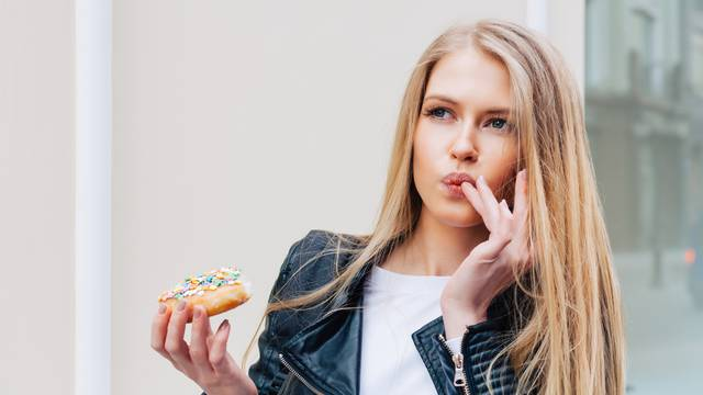 Beautiful young sexy woman eating a donut, licking her fingers taking pleasure a European city street. Outdoor. Warm color.