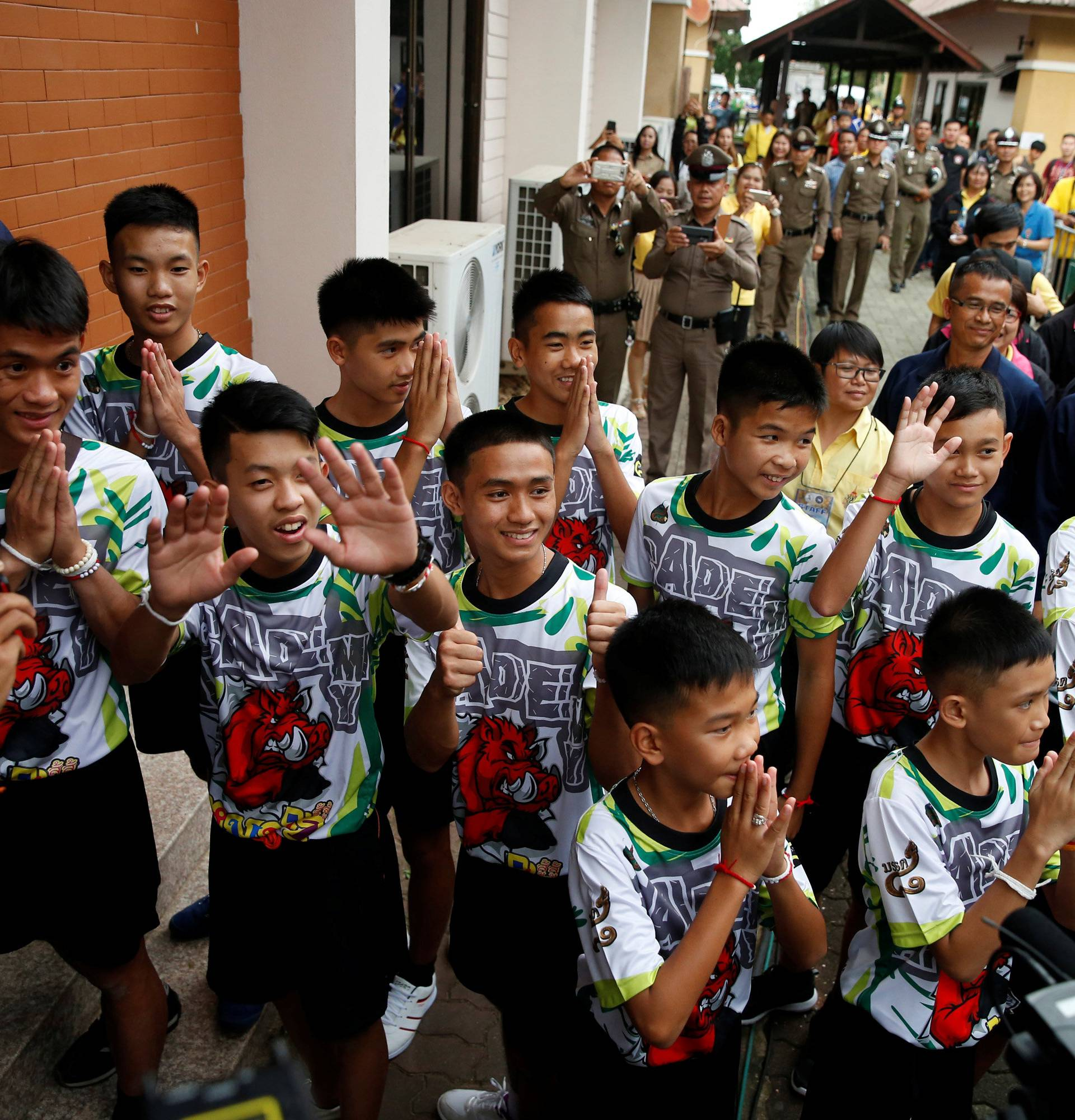 The 12 boys and their soccer coach who were rescued from a flooded cave arrive for a news conference in the northern province of Chiang Rai