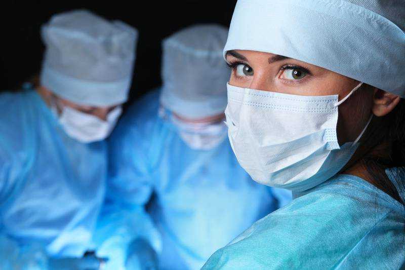 Closeup of surgeons performing operation. Focus on female nurse. Medicine, surgery and emergency help concepts