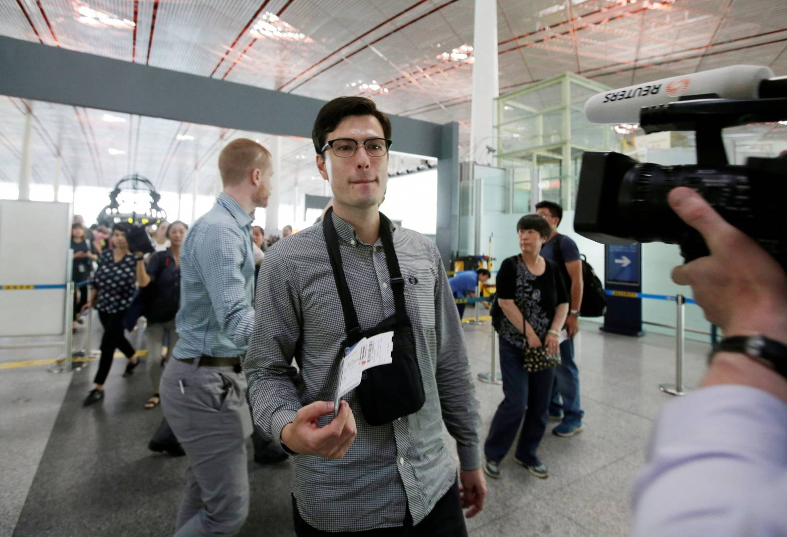 An Australian student Alek Sigley, 29, who was detained in North Korea, looks at the media member as he departs from Beijing to Japan, at the Beijing international airport