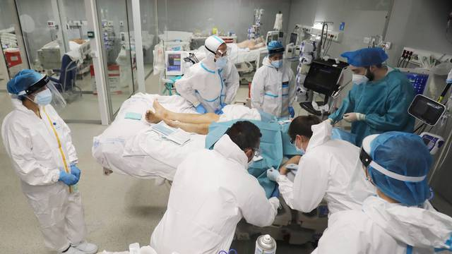 Medical staff members attend a COVID-19 patient inside the ICU ward at Nurse Isabel Zendal new pandemic hospital in Madrid