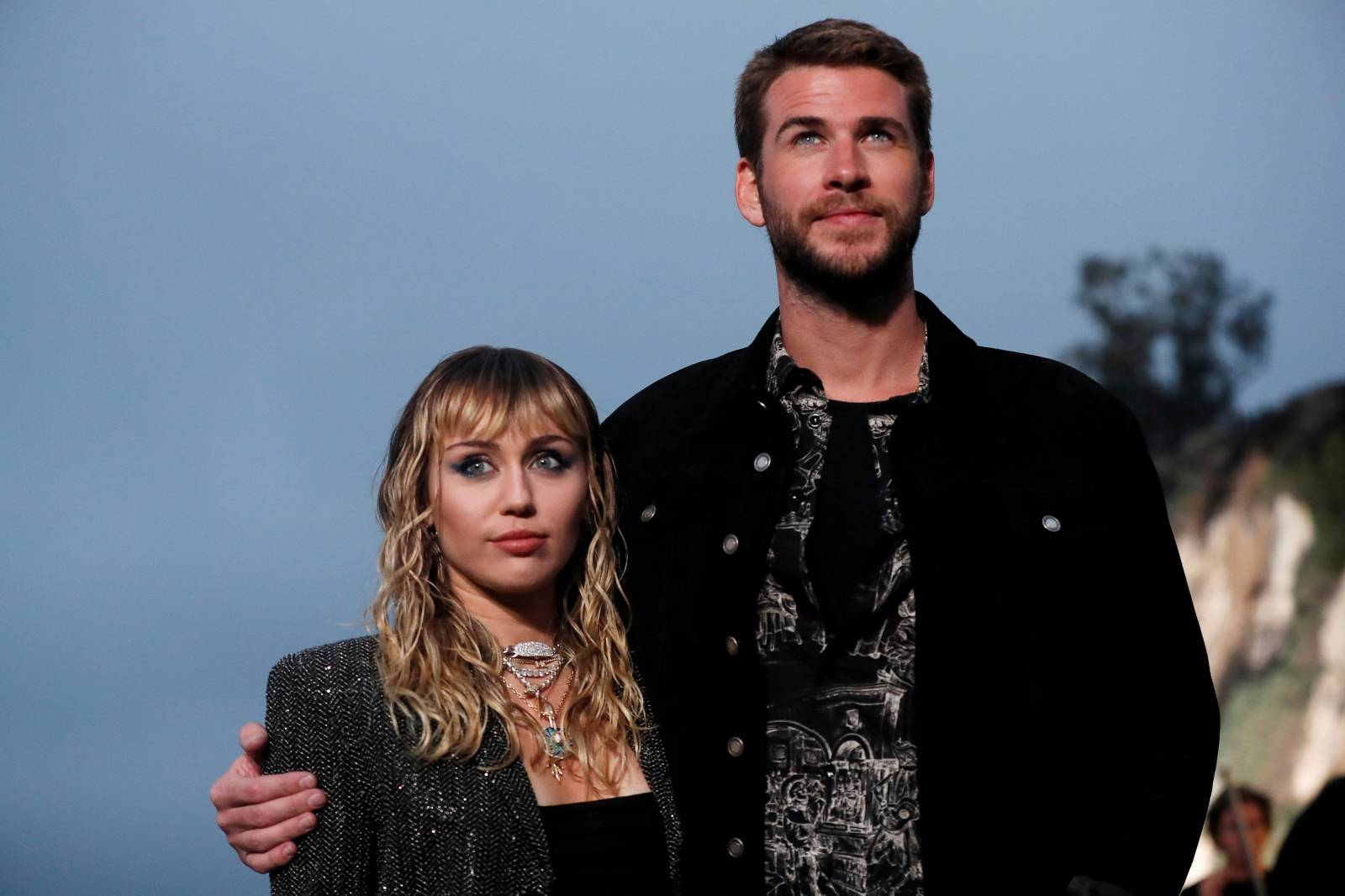 Miley Cyrus and Liam Hemsworth look on at the Saint Laurent Men's Spring/Summer 2020 fashion show at Paradise Cove beach in Malibu
