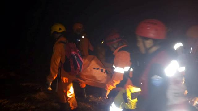 Rescue workers carry a body bag containing a victim following the collapse of an illegal gold mine at Bolaang Mongondow regency in North Sulawesi