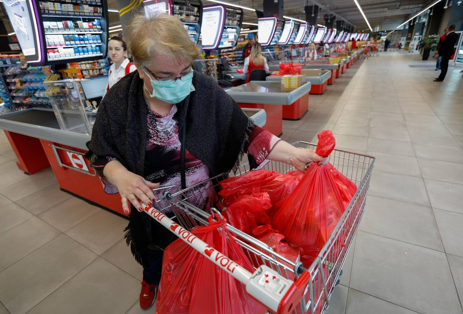 A woman wears a mask as she packs her groceries after the government limited the number of customers in supermarkets to 50 at a time due to coronavirus (COVID-19) threat in Podgorica
