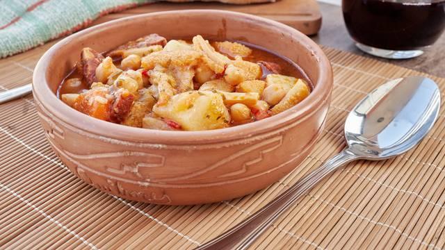 Mondongo a la espanola or cayos a la espanola. Presented in an earthenware bowl, on a wooden table View at 45 degrees.