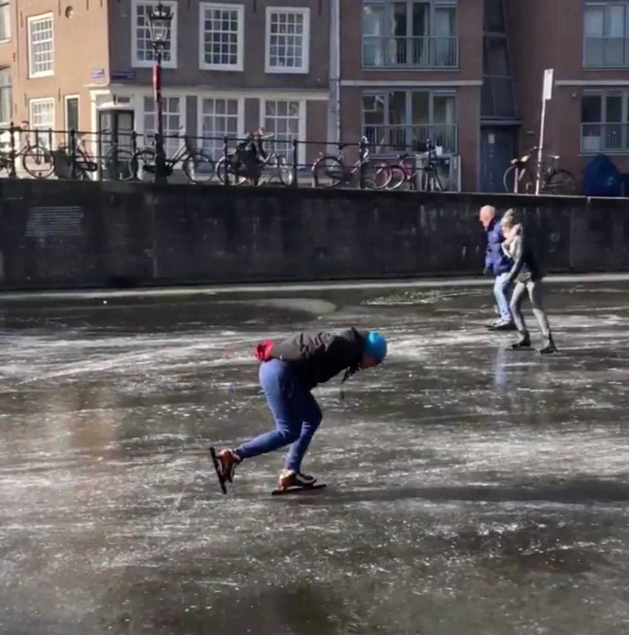 People skate on the frozen canal in Amsterdam