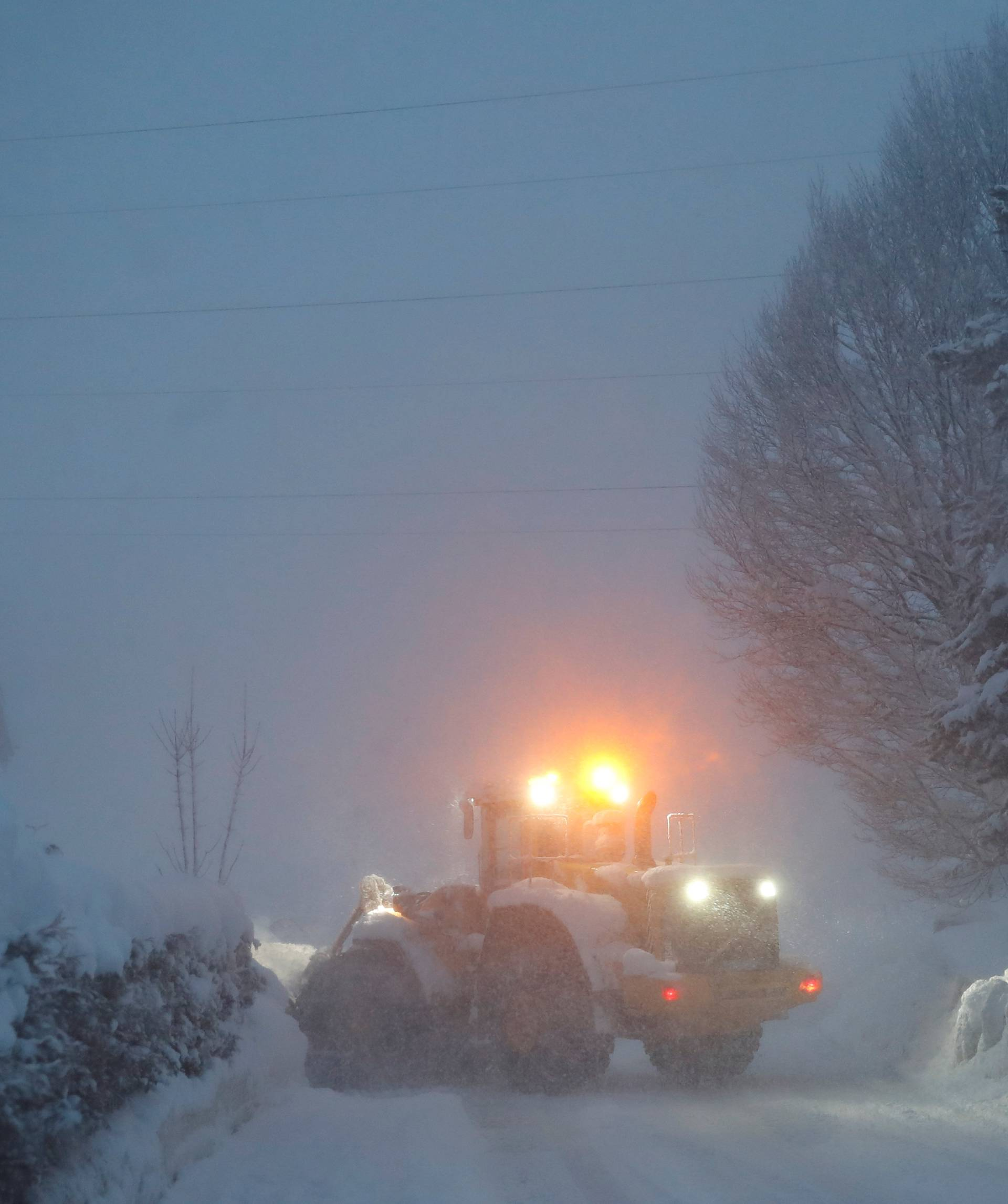 A vehicle removes snow from a road during heavy snowfall in Reitdorf