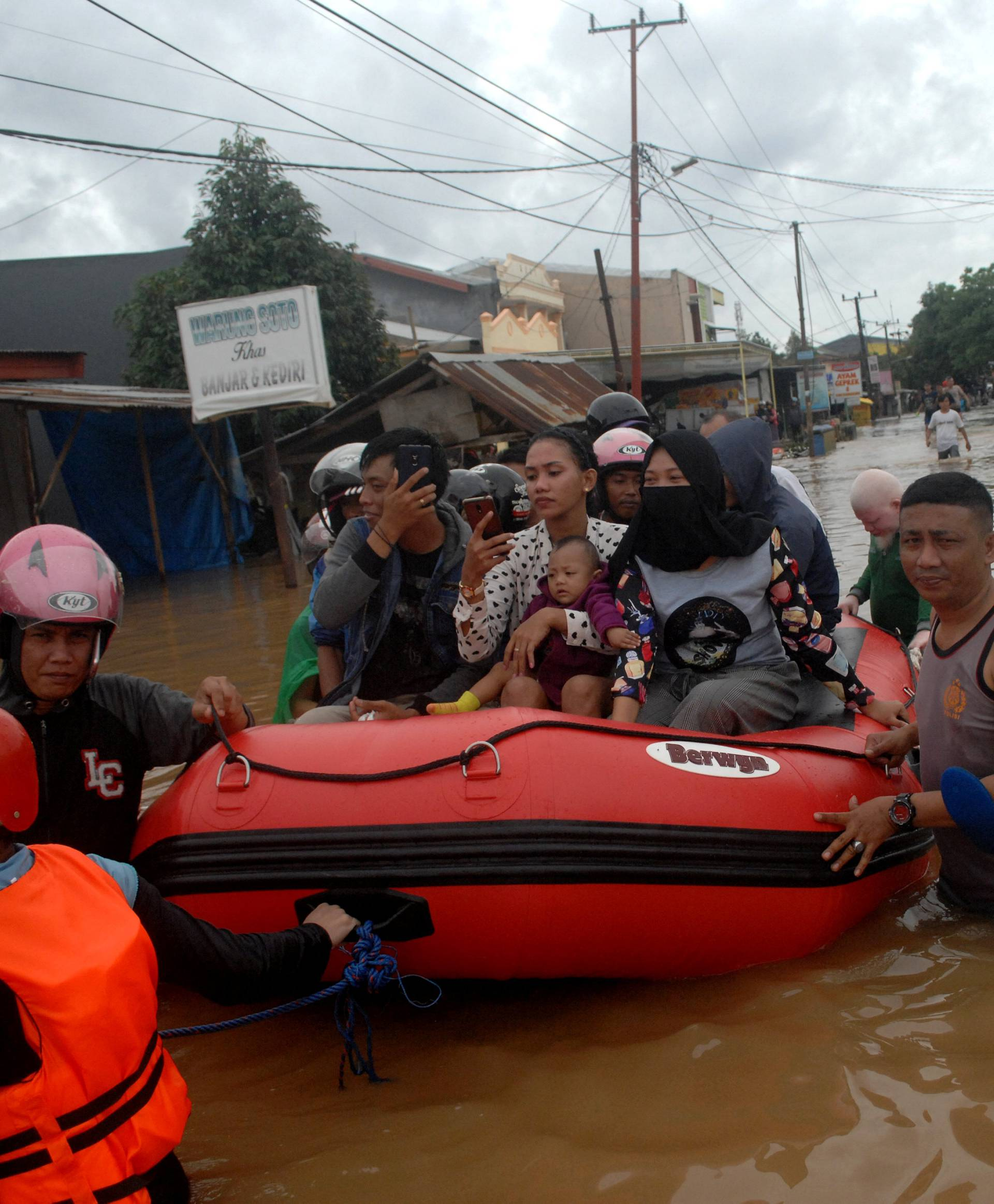 Rescue workers push an inflatable boat as they evacuate residents following floods in Makassar