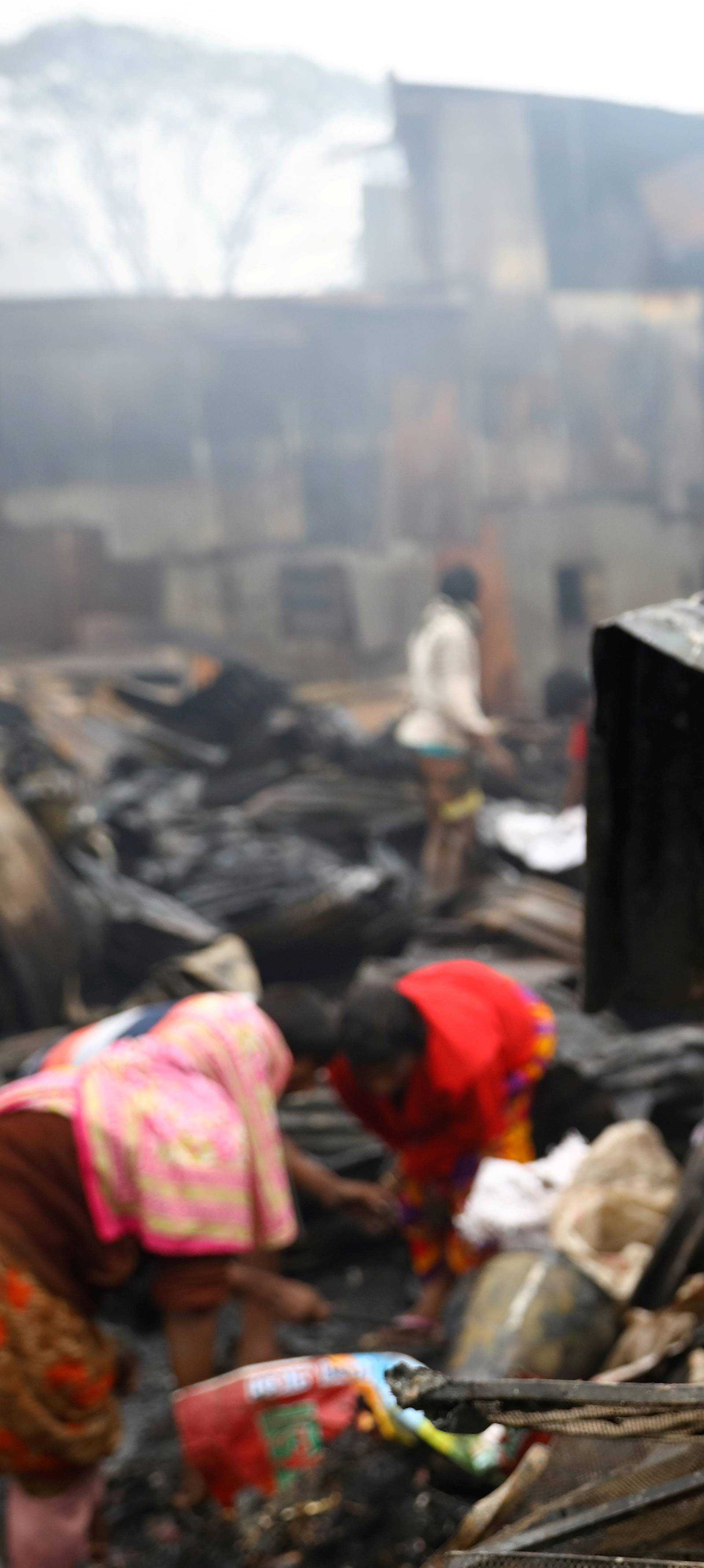 Child looks on, whose shelter has been burned after a fire broke out in a slum in Dhaka