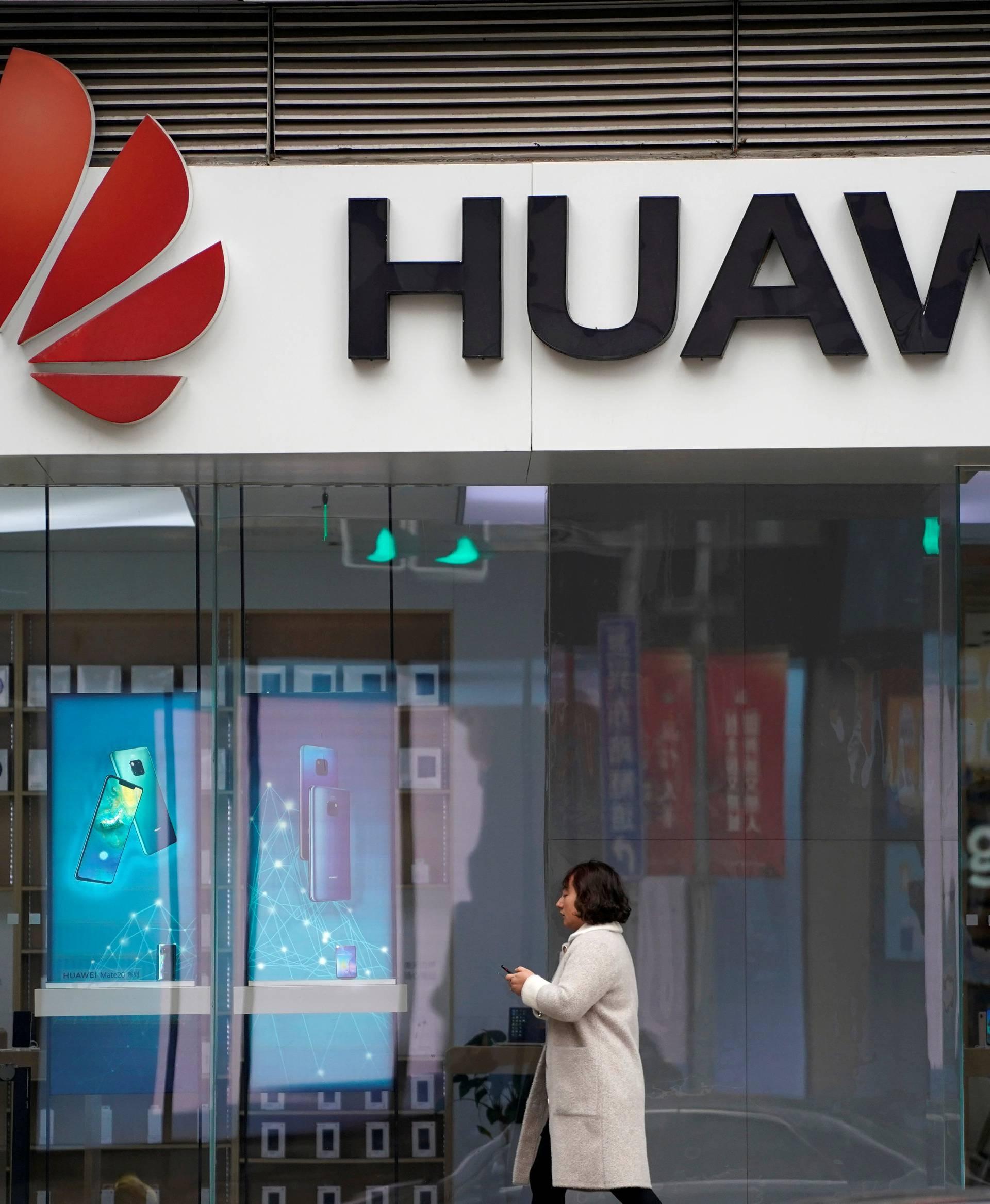 FILE PHOTO: A woman walks by a Huawei logo at a shopping mall in Shanghai