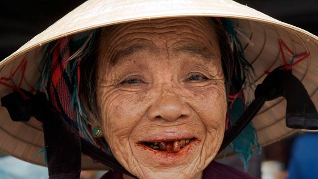 Aged woman with red betel nut stains in her mouth, Hoi An, Vietnam