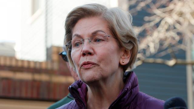 FILE PHOTO: Senator Elizabeth Warren talks to reporters after telling her staff she is withdrawing from 2020 U.S. presidential race outside her home in Cambridge, Massachusetts