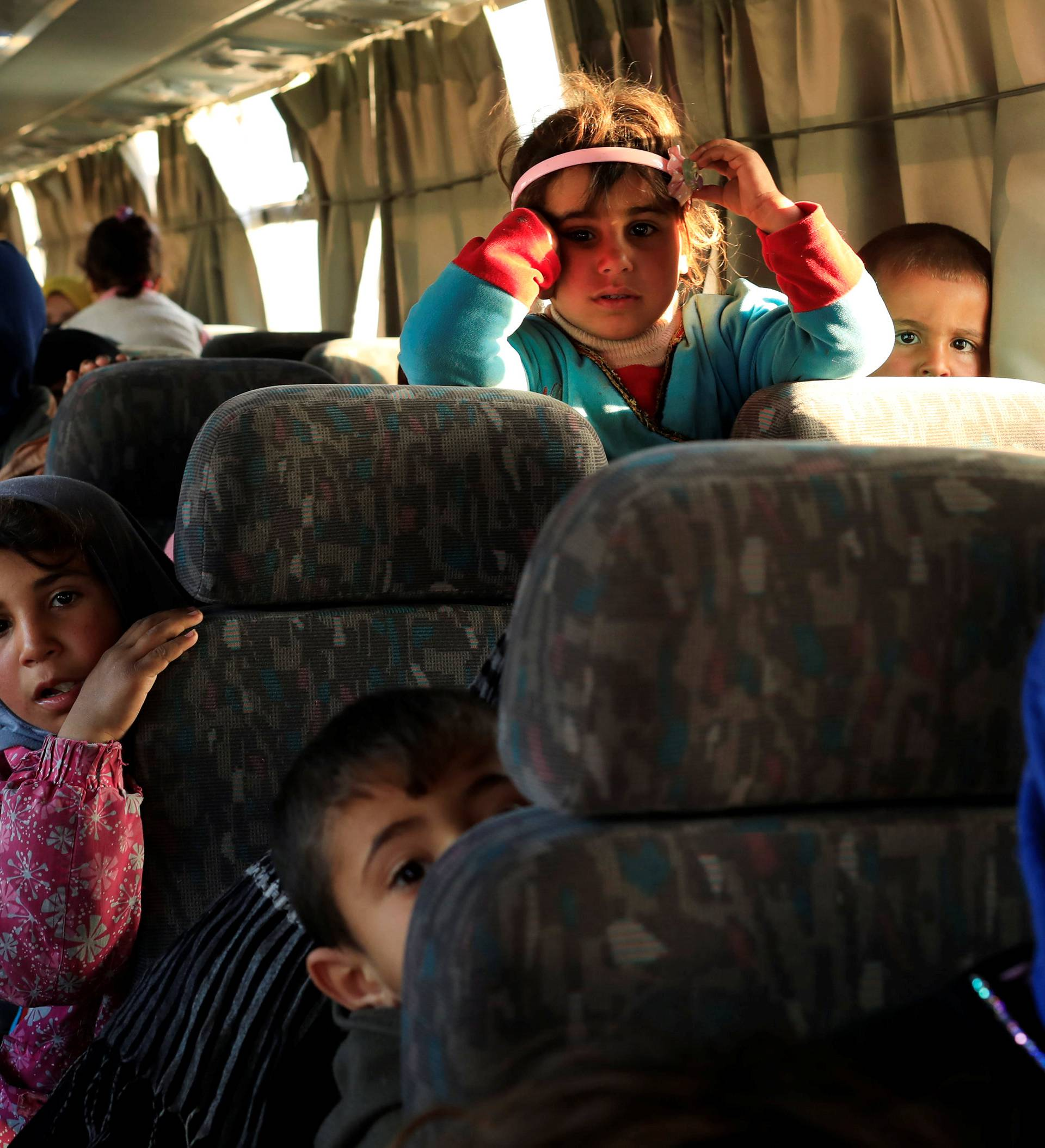 People, who just fled a village controled by Islamic State militants, sit inside a bus before heading to a camp at Hammam Ali, south of Mosul