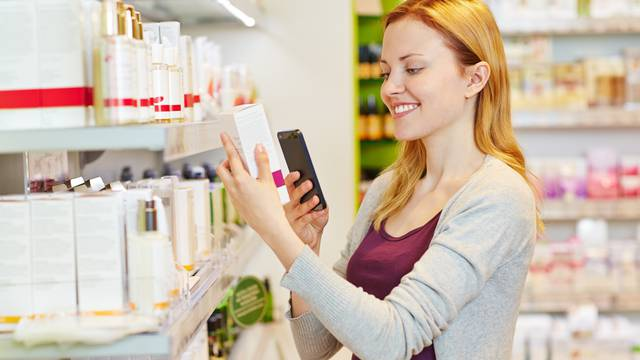 Woman comparing prices with smartphone in drugstore