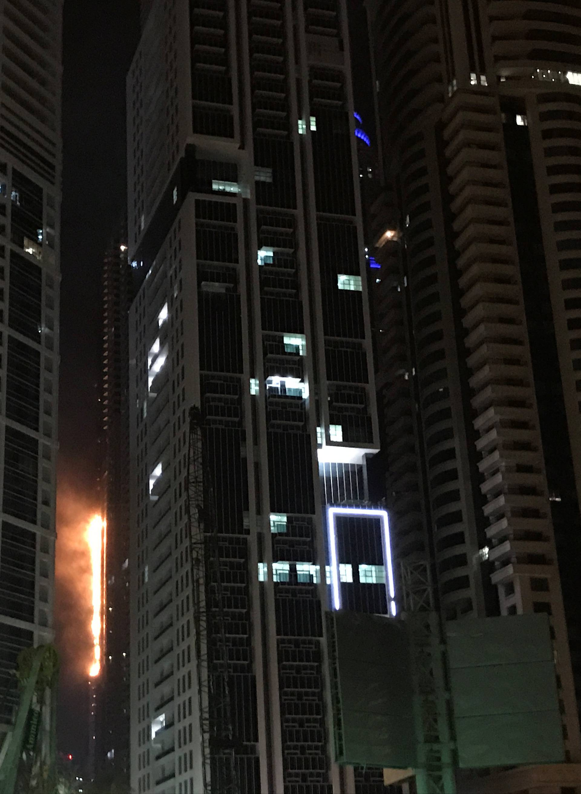 Flames shoot up the side of the Torch tower residential building in the Marina district, Dubai