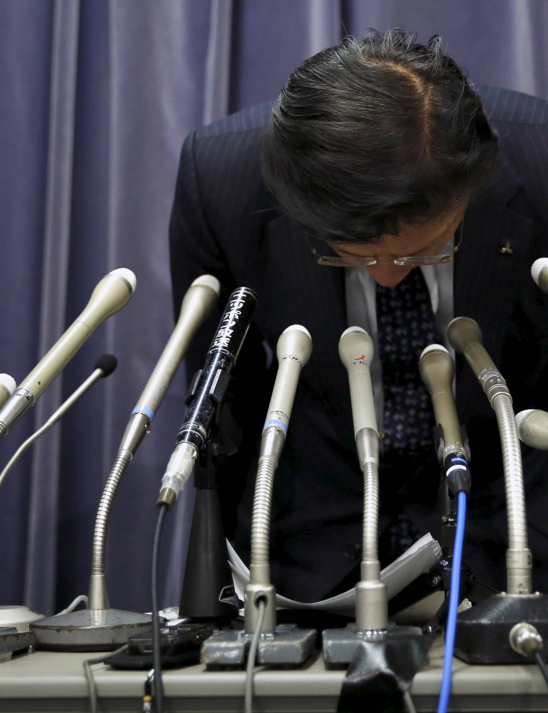 Mitsubishi Motors Corp's President Tetsuro Aikawa bows as he leaves a news conference to brief about issues of misconduct in fuel economy tests at the Land, Infrastructure, Transport and Tourism Ministry in Tokyo
