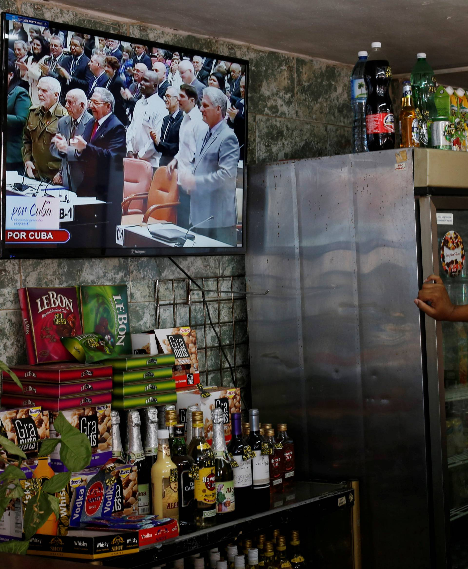 Cuba's President Raul Castro and  First Vice-President Miguel Diaz-Canel are seen on a TV screen inside a restaurant during a session of the National Assembly in Havana