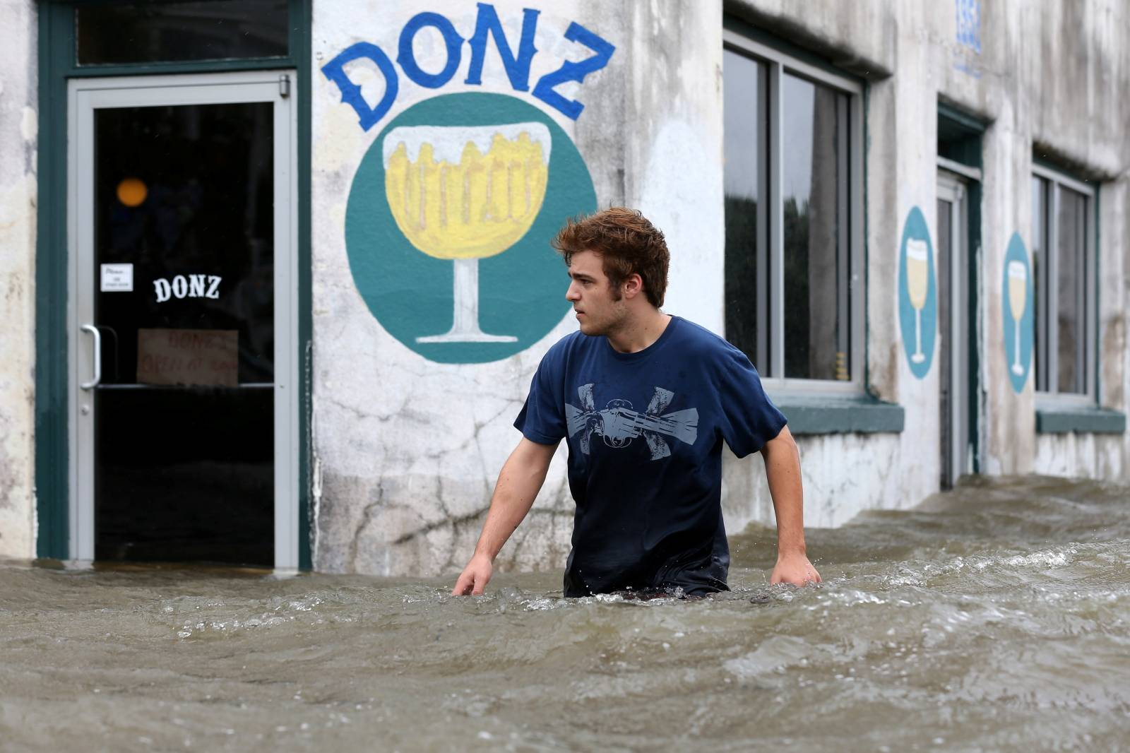 Logan Courvlle walks in front of a flooded business after Hurricane Barry in Mandeville