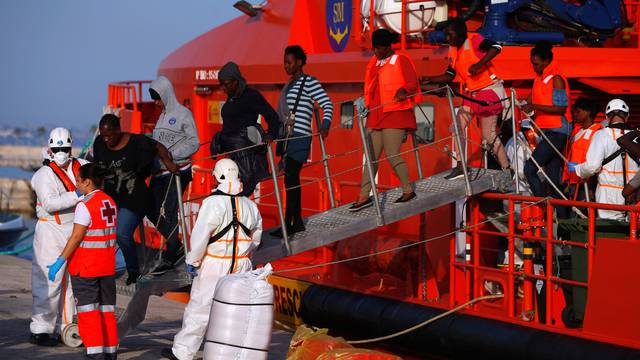 Migrant women leave a rescue boat after arriving at the port of Malaga