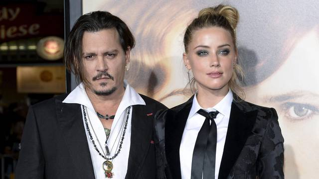 "Cast member Amber Heard and husband Johnny Depp pose during the premiere of the film ""The Danish Girl,"" in Los Angeles"