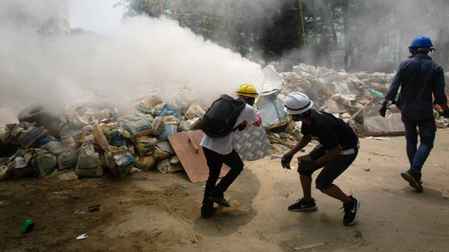 Protesters use fire extinguishers during a protest against the military coup in Yangon