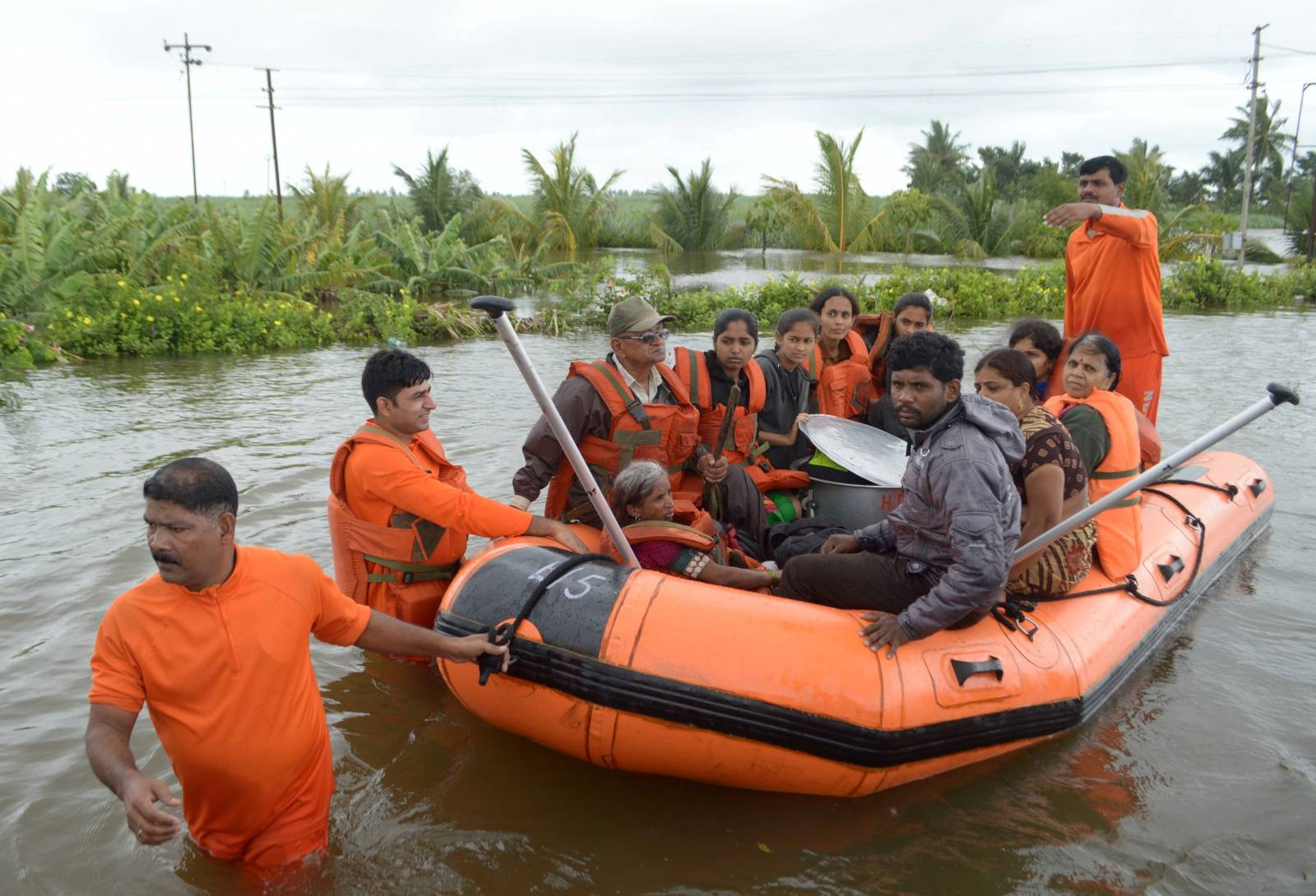 Members of National Disaster Response Force evacuate flood-affected people to a safer place, in Sangliwadi in Sangli district