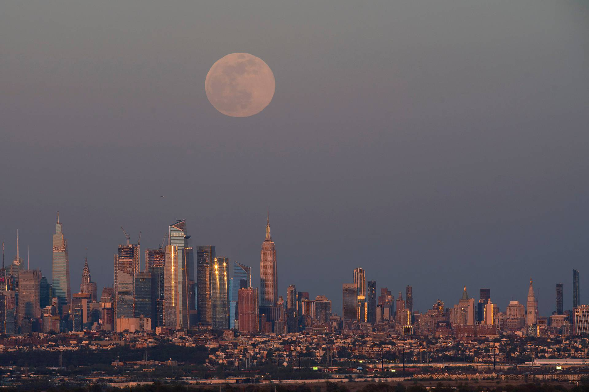 "The full moon, known as the ""Super Pink Moon"", rises over the skyline of New York and Empire State Building, as seen from West Orange, in New Jersey"