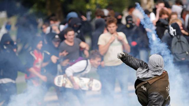 A demonstrator throws back a tear gas during a national strike and protest against the government's labour reforms in Nantes