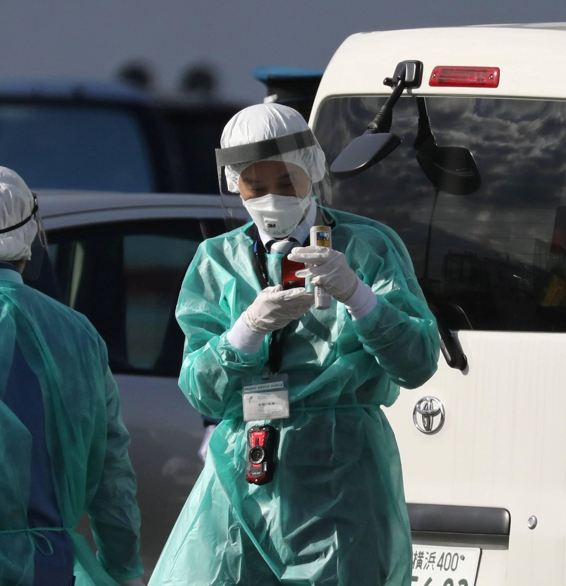 Health officials dressed in protective gear are seen near the cruise ship Diamond Princess at Daikoku Pier Cruise Terminal in Yokohama