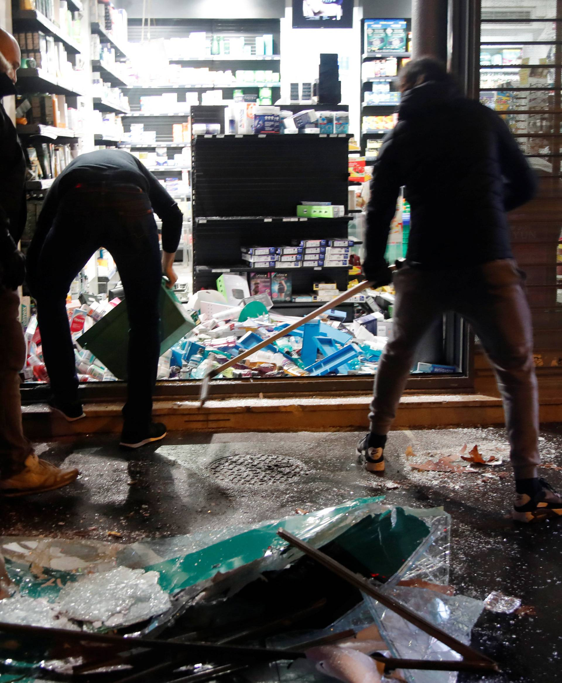 People try to clean uo a destroyed shop window on avenue Kleber after clashes with protesters wearing yellow vests, a symbol of a French drivers' protest against higher diesel taxes, in Paris