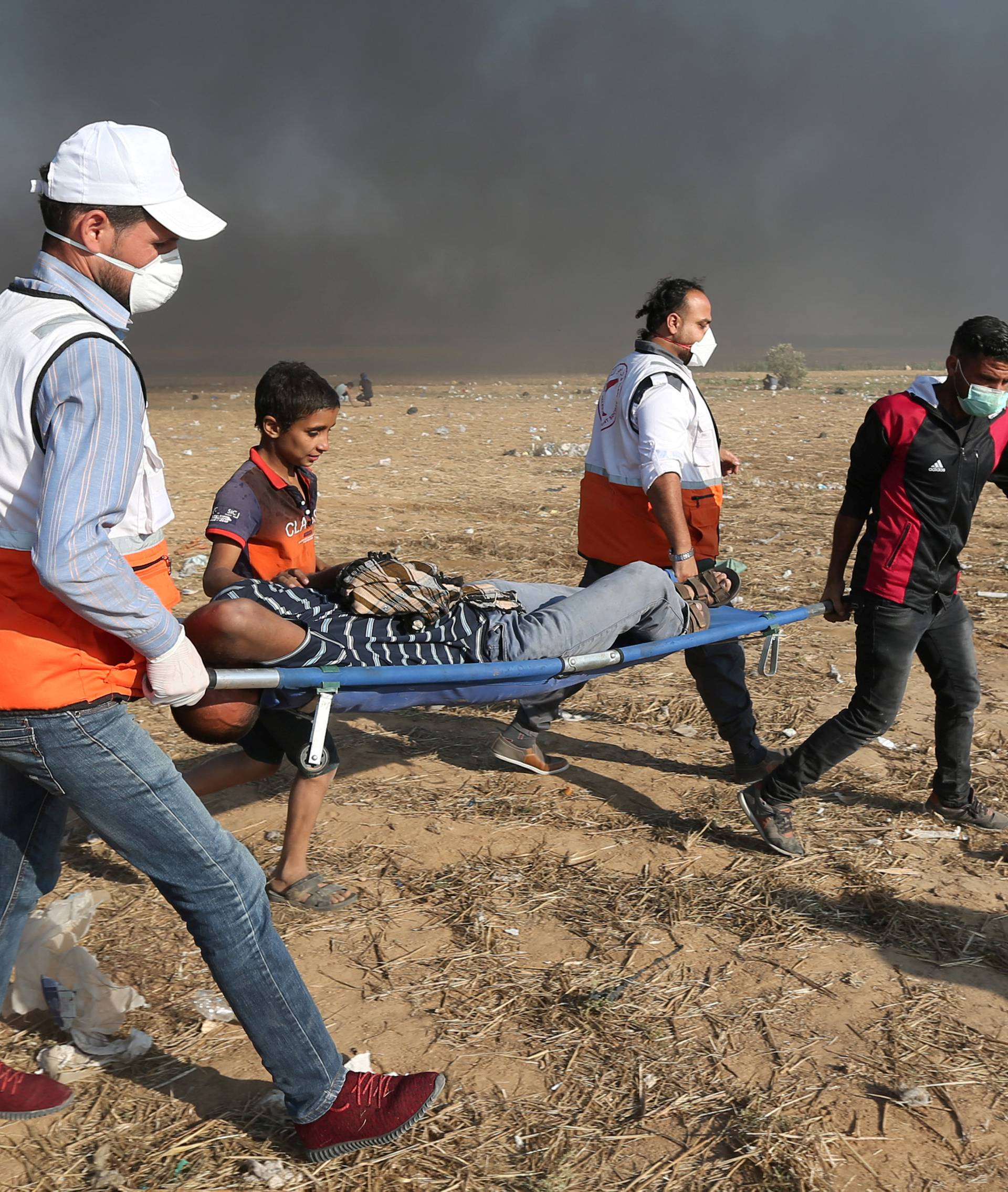 Wounded Palestinian demonstrator is evacuated after inhaling tear gas fired by Israeli troops during a protest marking the 70th anniversary of Nakba, at the Israel-Gaza border in the southern Gaza Strip