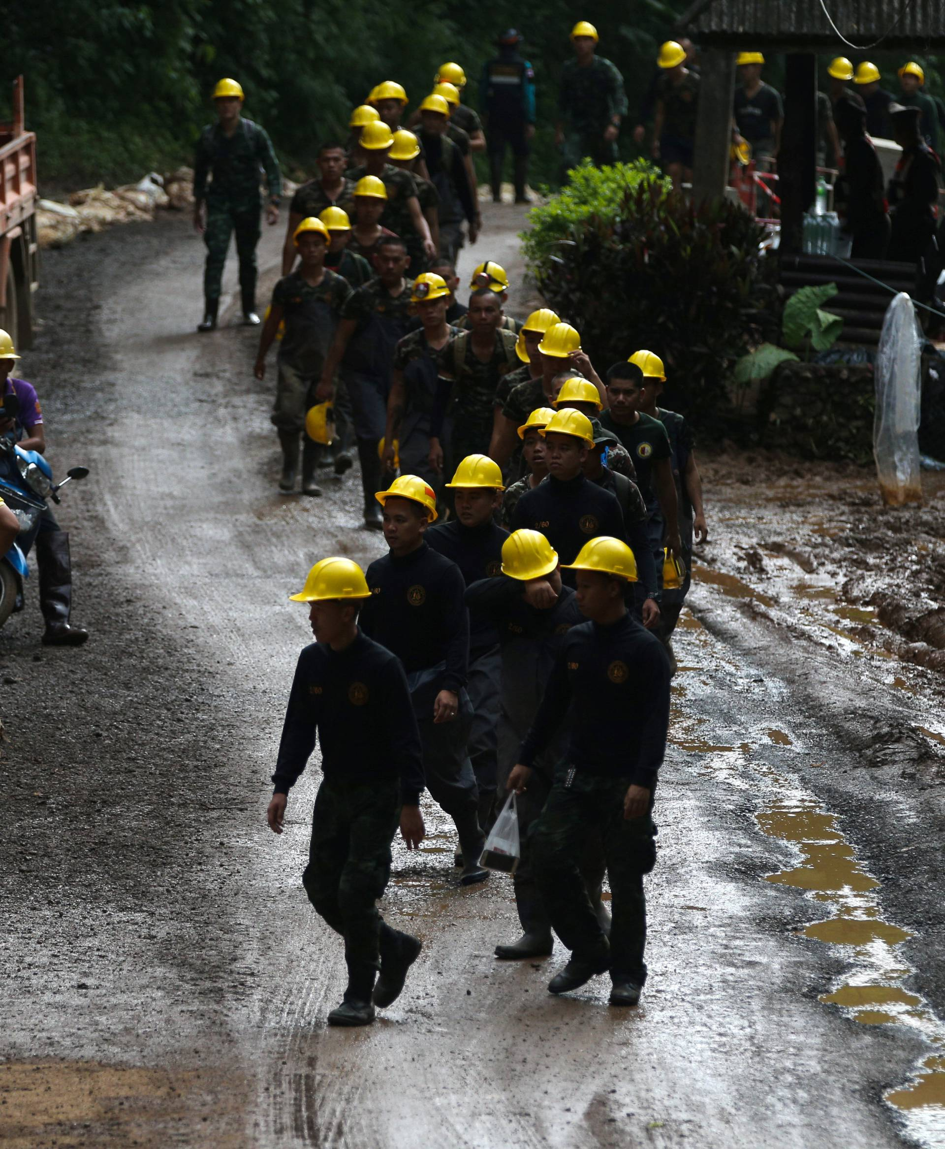 Military personnel walk in line as they prepare to enter the Tham Luang cave complex, where 12 boys and their soccer coach are trapped, in the northern province of Chiang Rai
