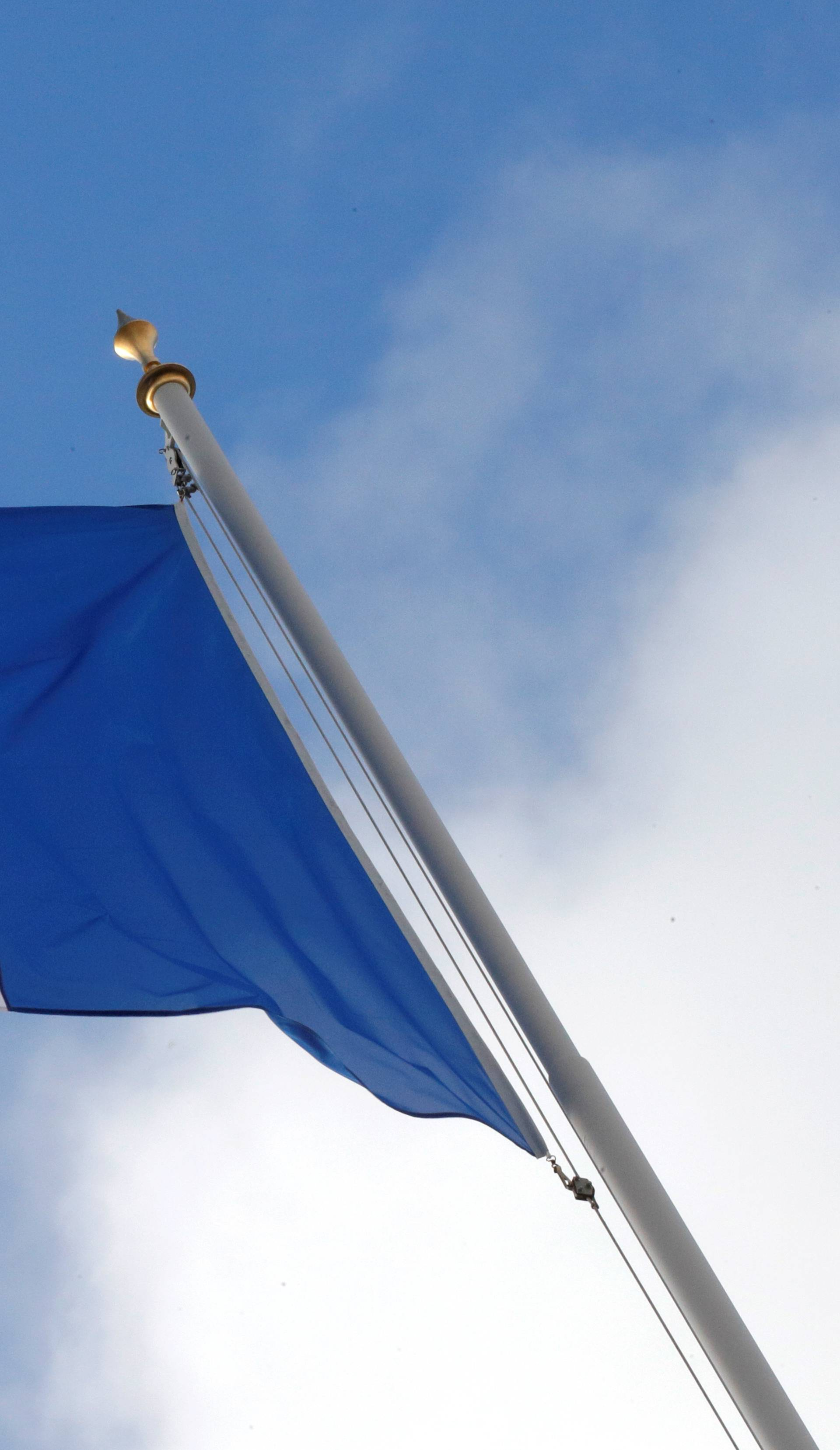 FILE PHOTO: A French flag flutters in the sky over the Elysee Palace in Paris
