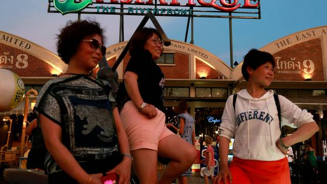 Tourists pose for a photo at Asiatique night market, in Bangkok