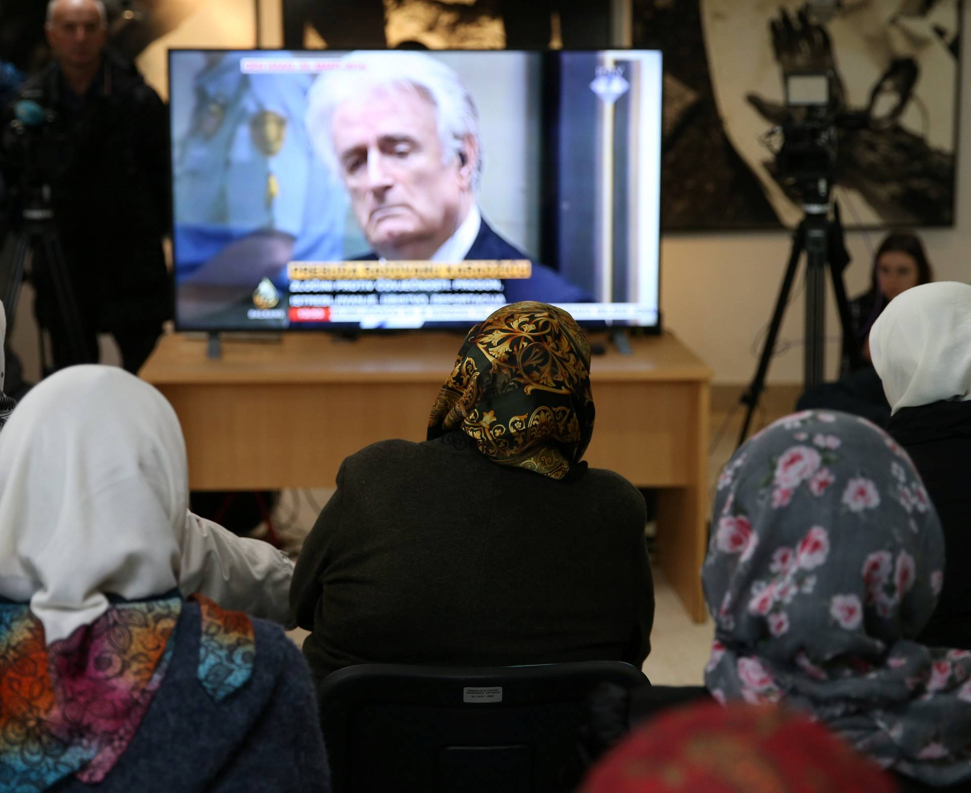 People wait for the judges verdict on former Bosnian Serb political leader Radovan Karadzic's appeal of his 40 year sentence for war crimes, in the Memorial centre Potocari near Srebrenica