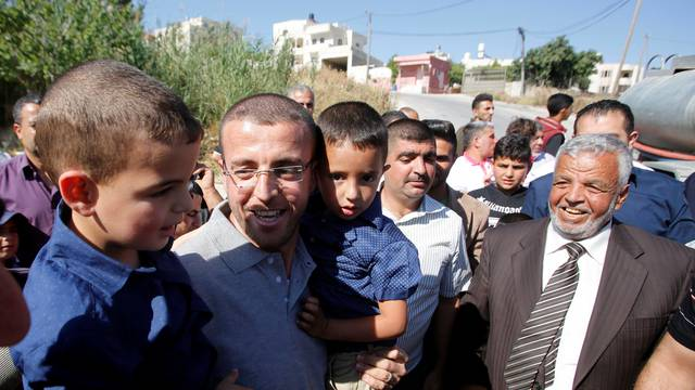 Freed Palestinian journalist Mohammad al-Qiq, who was detained by Israel last November and went on 94-day hunger strike to protest against his detention without charge, holds his children upon his release in the West Bank town of Dura