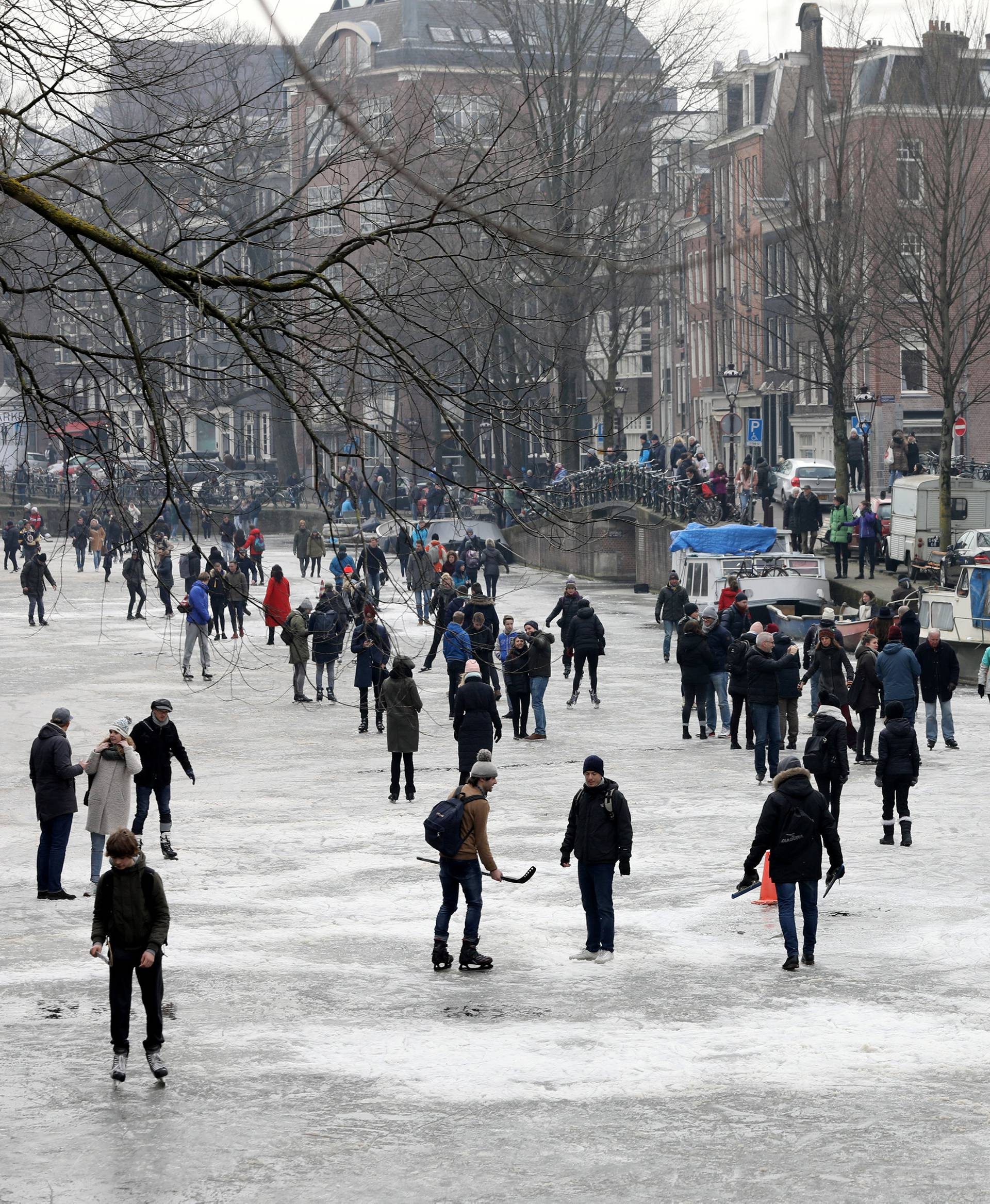 Ice skaters skate on frozen canal during icy weather in Amsterdam